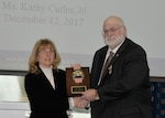 Steve Sherman receives his retirement plaque from DLA Information Operations Chief Information Officer Kathy Cutler Dec. 12, after 38 years of federal service.