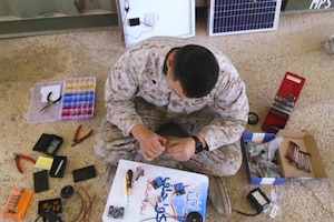 A Marine sitting on the ground with 3D printed materials, wires and tools.