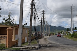 USACE Task Force Power Restoration Commander Col. John P. Lloyd (foreground) and TF Power Operations Officer Capt. Aaron Anderson survey the damage wrought by Hurricane Maria as they walk through a neighborhood in Maunabo, Puerto Rico, on Jan. 3. To date, Anderson's team has set-up microgrids in five locations, starting with Culebra Island. The next four were placed in the Southeast, which was ground zero, sustaining tremendous damage when Hurricane Maria made landfall. These microgrids are operating in Patillas, Maunabo, Naguabo and Yabucoa, Puerto Rico.