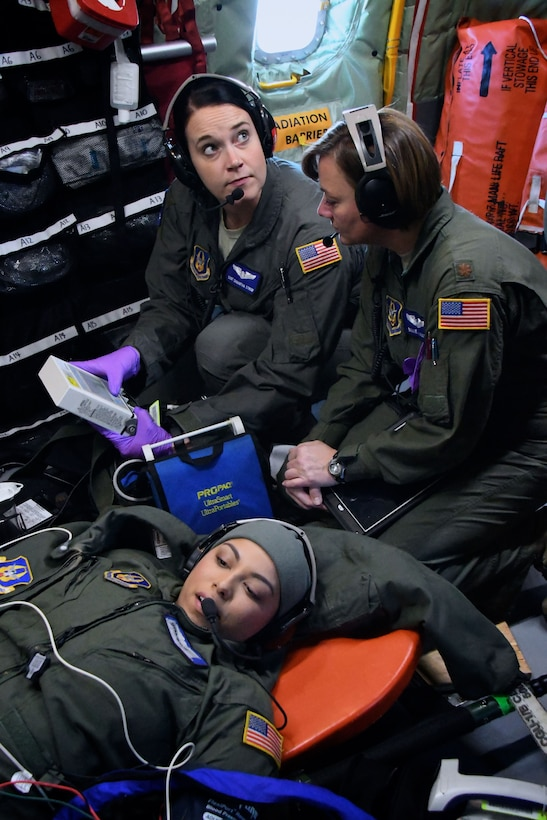 """Providing care in the air at 25,000 feet are Staff Sgt. Samantha Strom and Maj. Billie Vogt, 932nd Airlift Wing Aeromedical Evacuation Squadron members.  Together they discuss with other members on radio communication headsets to consider various treatment possibilities for their """"simulated patient"""" during a training flight Dec. 16, 2017.  They trained alongside other nurses and medical technicians on a multi day mission with the 507th Air Refueling Wing aboard a KC-135 aircraft.  The 932nd Airlift Wing is a 22nd Air Force unit, under the Air Force Reserve Command and is located at Scott Air Force Base, Ill.  (U.S. Air Force photo by Lt. Col. Stan Paregien)"""