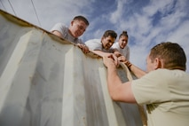 Arizona State University ROTC cadets help a teammate scale an obstacle during the 4th annual Luke Mudder competition at Luke Air Force Base, Ariz., Nov. 3, 2017. Working in teams of four, cadets competed for the fastest time to finish the 17 obstacle, mile and a half course. (U.S. Air Force photo/Airman 1st Class Caleb Worpel)
