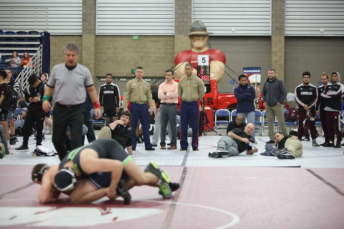 Gunnery Sgt. Gene Bradley and 1st Lt. Terrence Stephens watch wrestlers compete during the 2018 National Wrestling Coaches Association National Duals at the Allen County War Memorial Coliseum at Fort Wayne, Indiana, Jan. 4. Marines and wrestlers share similarities. The Marine Corps believes wrestlers possess certain characteristics and qualities that make them better suited for life as a Marine. (U.S. Marine Corps photo by Cpl. Quavaungh Pointer)