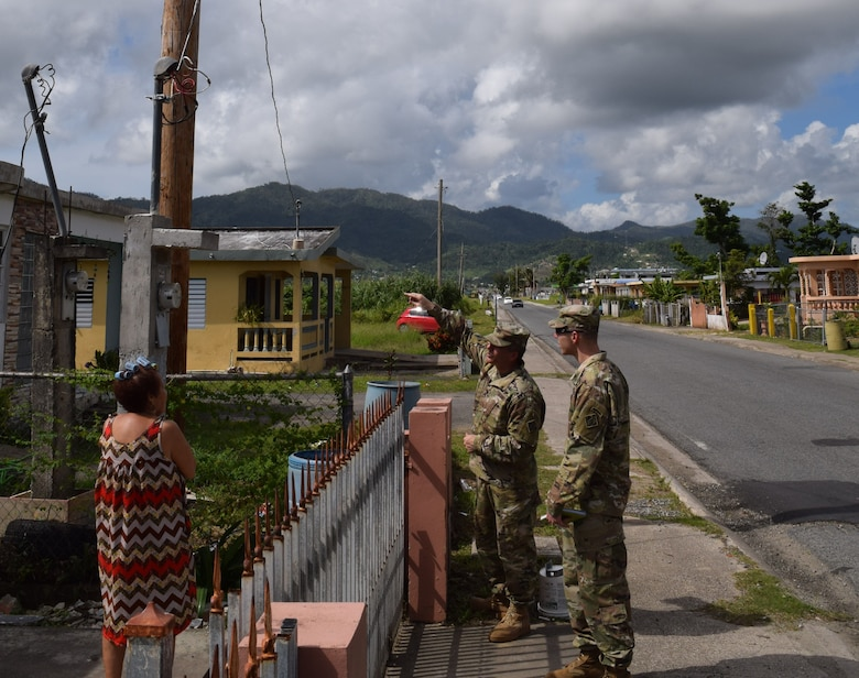"USACE Task Force Power Restoration Commander Col. John P. Lloyd, along with Capt. Aaron Anderson, TF Power operations officer, ask a resident in Maunabo, Puerto Rico, on Jan. 3, if she has power. Her reply: ""Yes, and thank you, thank you so much,"" Lloyd said. ""Microgrids are a great tool to help us service areas where main grid restoration is not projected to be complete in the near term,"" said Lloyd. ""Microgrids allow us to proof a distribution system in an area prior to main grid restoration so that when grid power is restored, there is less time spent having to diagnose the lines. The system is also very versatile, and may be a capability that can be used in future storms throughout the region."""
