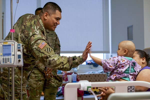 Army Sgt. Nathan Vaitautoiu high-fives a baby while visiting with her and her parents at a hospital in San Antonio, Jan. 2, 2018, during a 2018 U.S. Army All-American Bowl outreach event. Army photo by Sgt. Jonathan Fernandez