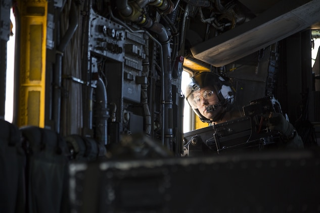 U.S. Marine Corps Lance Cpl. Kyle Missel, a crew chief assigned to Marine Heavy Helicopter Squadron (HMH) 465, looks inside the CH-53E Super Stallion as it flies above the Chocolate Mountain Aerial Gunnery Range, Dec. 9, 2017. HMH-465 arrived to MCAS Yuma, Nov. 29, 2017 to conduct training in support of Exercise Winter Fury. Exercise Winter Fury allows Marines to exercise the skills needed as the combat element of the Marine Air Ground Task Force during a combat deployment. (U.S. Marine Corps photo by Cpl. Isaac D. Martinez)