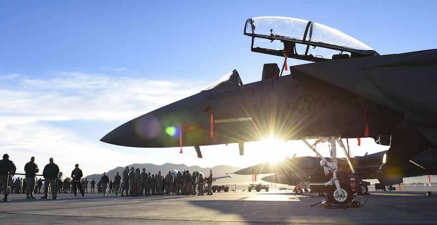 Airmen gather around an F-15C Eagle and an F-16 Fighting Falcon fighter jets after the quarterly load crew competition at Nellis Air Force Base, Nev., Jan. 5, 2018. All teams inspected, loaded and secured two bombs and one missile to their aircraft within an hour. (U.S. Air Force photo by Airman 1st Class Andrew D. Sarver/Released)