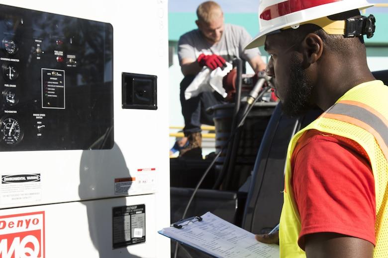 man inspects generator