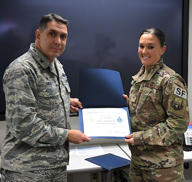 The commander of the 932nd Airlift Wing, Col. Raymond Smith, presents a certificate for the outstanding military bearing award to Staff Sergeant Nicole Frost Jan. 5, 2018, at Scott Air Force Base, Ill..  She also received a coin and another award for being an overall superior performer during the UEI capstone week, as chosen by the inspectors.  (U.S. Air Force photo by Lt. Col. Stan Paregien)