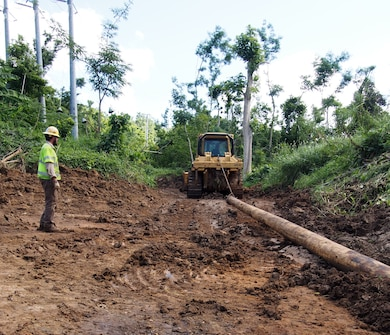 Emergency relief crews working with Army Corps of Engineers, Task Force Power Restoration, pull a wooden power pole up a newly created road to as part of the ongoing effort to restore power to the Trujillo Alto, Puerto Rico, Christmas Eve, 2017.  USACE is partnering with the Puerto Rico Electric Power Authority, the Department of Energy and FEMA and contracted partners, to restore safe and reliable power to the people of Puerto Rico. As assigned by FEMA, USACE leads the federal effort to repair the hurricane-damaged electrical power grid in support of the Government of Puerto Rico. Puerto Rico Electric Power Authority reports 59.4 percent or 875,500 of the 1.47M customers who are able to receive electric power have their service restored.