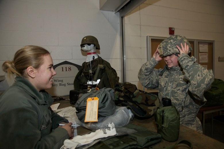 Airman 1st Class Melissa Alotta, 191st Maintenance Squadron, tries on a helmet while receiving her protective chemical warfare gear at Selfridge Air National Guard Base, Mich., Jan. 6, 2018. Issuing the equipment is Airman 1st Class Sarah Henkel, 127th Logistics Readiness Squadron