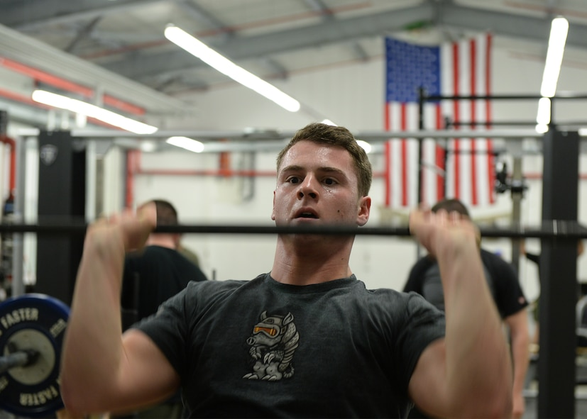 Senior Airman Logan Keller, 786th Civil Engineer Squadron explosive ordinance disposal technician, performs a push-press during an EOD Fallen Warrior Workout on Ramstein Air Base, Germany, Jan. 5, 2018. For the event, 12 teams of three Airmen competed to see who could finish the entire workout as a team the fastest. (U.S. Air Force photo by Senior Airman Jimmie D. Pike)