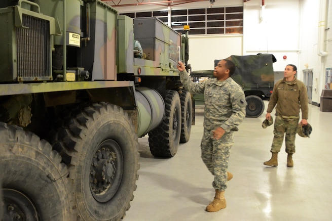 Guardsmen look at a military vehicle.