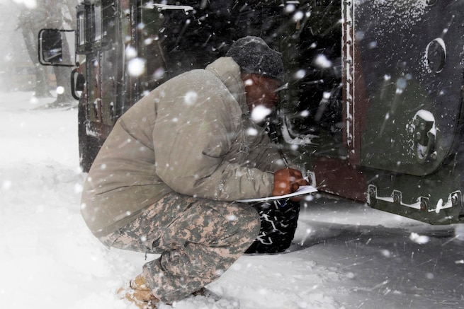 New York Army National Guard Sgt. Ashaun Howard performs last minute checks on Humvees.