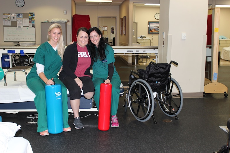 U.S. Air Force Medical Service Corps Officer, Maj. Stephanie Proellochs (center), works with two of Walter Reed National Military Medical Center's physical therapists in Bethesda, MD, Nov. 8, 2017. Kyla Dunlavey (right) and Alyssa Olsen (left) work with the rest of Proellochs' medical team throughout her amputation recovery.  Proellochs was diagnosed with a metastatic tumor in her left foot in January 2017, which resulted in having her foot amputated. (U.S. Air Force photo by Karina Luis)