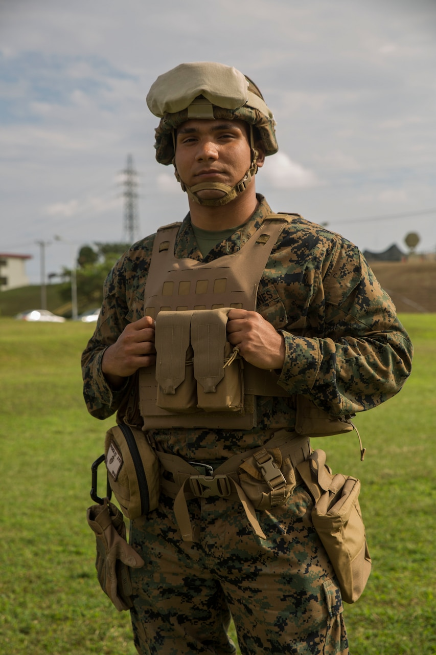 Marine in battle gear poses for a photo in Okinawa, Japan.