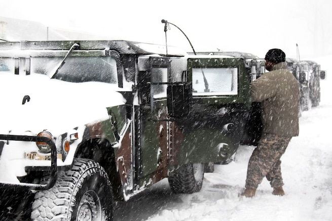 A guardsman opens the door to a Humvee during a snowstorm.