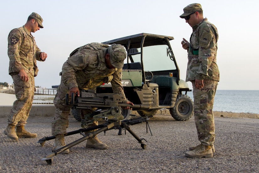 Three Soldiers assembling a grenade launcher.