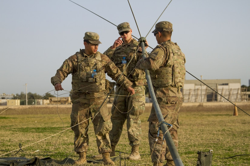 Three Soldiers setting up a radio communications antenna.