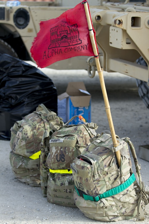 Three backpacks sitting on the ground, one with a flag sticking out.