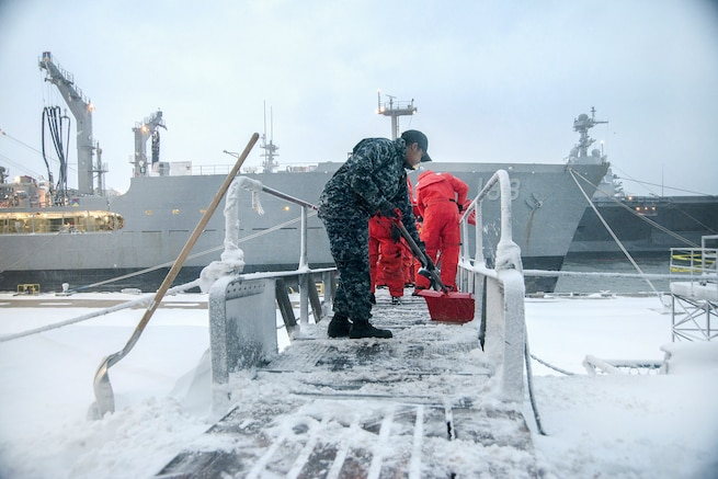 Sailors shovel snow off the walkway to a ship.