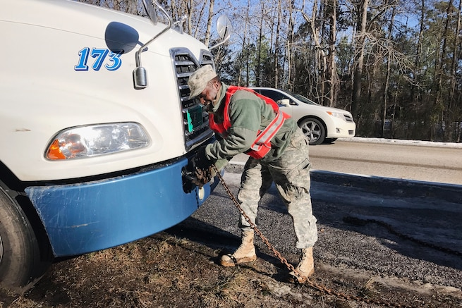 A guardsman attaches a chain to the front of an 18-wheeler.
