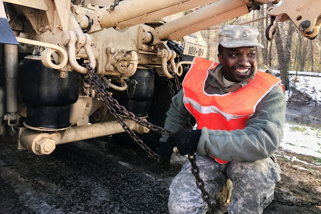A soldier attaches a chain to a vehicle.