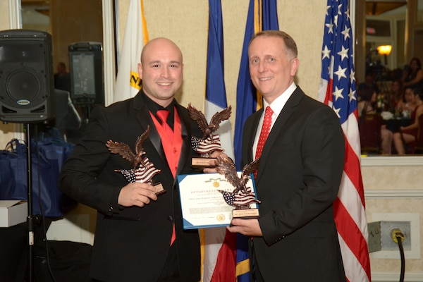 """Petty Officer 1st Class Raymond Gonzalez (left), a Navy recruiter assigned to Navy Recruiting Station McAllen, Navy Recruiting District San Antonio, stands with Commanding Officer Cmdr. Jeffrey Reynolds after being awarded NRD's Enlisted Recruiter, Enlisted Female Upper Mental Group Recruiter, and Diversity Recruiter of the Year for Fiscal Year 2017 during the NRD's annual award banquet held at the Crowne Plaza Hotel in Austin Dec. 19, 2017. """"I chose to steer my career in the direction of recruiting to make a difference in the recruiting community,"""" said Gonzalez, who will be graduating from Post University in 2019 with a bachelor's degree in criminal justice. """"My goal in recruiting is strictly to be an honest and unaggressive outlet of information for young adults to confidently explore their career options."""" Additionally, Gonzalez was awarded the Navy and Marine Corps Commendation Medal for his superior performance of duty."""