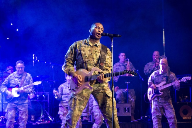 A soldier plays guitar and sings as fellow soldiers play guitar behind him on a blue-lit, smoky stage.