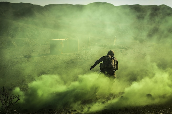A soldier, shown from behind, runs as yellowish-green smoke billows around him.