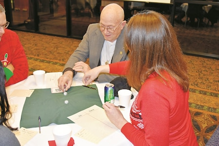 John Bonacorda, retired Chief Warrant Officer 2 and Vietnam War Veteran, tries his hand at Bunco, a dice game that uses three dice. It was the first time playing the game for the former UH-1 Crew Chief and Door Gunner.