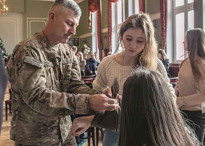 Capt. Charles Powell, left, physician assistant with 82nd Brigade Engineer Battalion, 2nd Armored Brigade Combat Team, 1st Infantry Division, from Fort Riley, shows Maja Kowalska, a student at Zary, Poland School District No. 5, how to properly apply a improvised dressing to an arm wound during first aid training held at Żary City Hall Dec. 8.