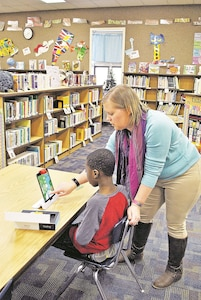 Emily Warren, instructional coach, helps Emmanuel Sokoye-Patoki, 6, son of Staff Sgt. Abalo Sokoye- Patoki, 41st Engineer Company (Clearance), 1st Engineer Battalion, 1st Armored Brigade Combat Team, 1st Infantry Division, during the Hour of Code event Dec. 4 at Jefferson Elementary School library.