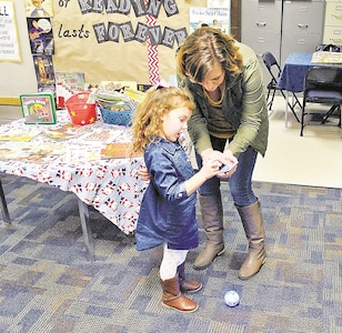 Casyn Miles, 5, daughter of Staff Sgt. Jason Simmer, Company A, 1st Combined Arms Battalion, 63rd Armor Regiment, 2nd Armored Brigade Combat Team, 1st Infantry Division, and her mother Christy Simmer try and figure out how to program a lighted sphere during the Hour of Code event Dec. 4 at Jefferson Elementary School library.