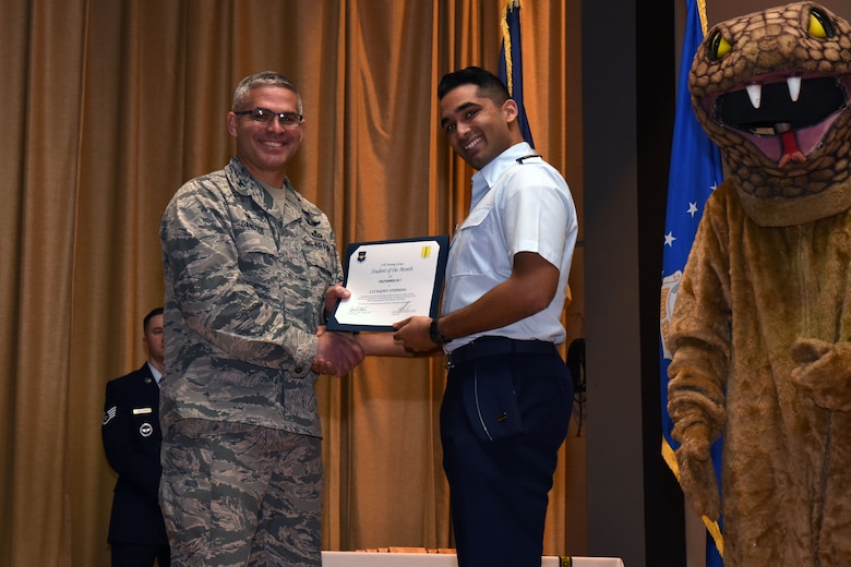 U.S. Air Force Col. Alex Ganster, 17th Training Group commander, presents the 315th Training Squadron Officer Student of the Month award for Dec. 2017 to 2nd Lt. Rajeev Stephens, 315th TRS trainee, in the base theater on Goodfellow Air Force Base, Texas, Jan. 5, 2018. The 315th Training Squadron's mission is to train, educate and mentor our future intelligence, surveillance and reconnaissance warriors through innovation. (U.S. Air Force photo by Airman 1st Class Seraiah Hines/Released)