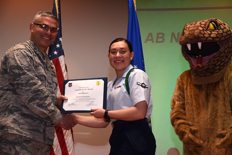 U.S. Air Force Col. Alex Ganster, 17th Training Group commander, presents the 315th Training Squadron Student of the Month award for Dec. 2017 to Airman Nina Bleckley, 315th TRS trainee, in the base theater on Goodfellow Air Force Base, Texas, Jan. 5, 2018. The 315th Training Squadron's vision is to develop combat-ready intelligence, surveillance and reconnaissance professionals and promote an innovative squadron culture and identity unmatched across the United States Air Force. (U.S. Air Force photo by Airman 1st Class Seraiah Hines/Released)