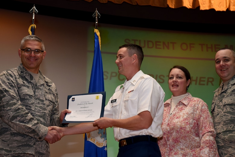 U.S. Air Force Col. Alex Ganster, 17th Training Group commander, presents the 312th Training Squadron Student of the Month award for Dec. 2017 to U.S. Army Spc. Christopher Dennis, 312th TRS trainee, in the base theater on Goodfellow Air Force Base, Texas, Jan. 5, 2018. The 312th Training Squadron's mission is to provide Department of Defense and international customers with mission ready fire protection and special instruments graduates and provide mission support for the Air Force Technical Applications Center. (U.S. Air Force photo by Airman 1st Class Seraiah Hines/Released)