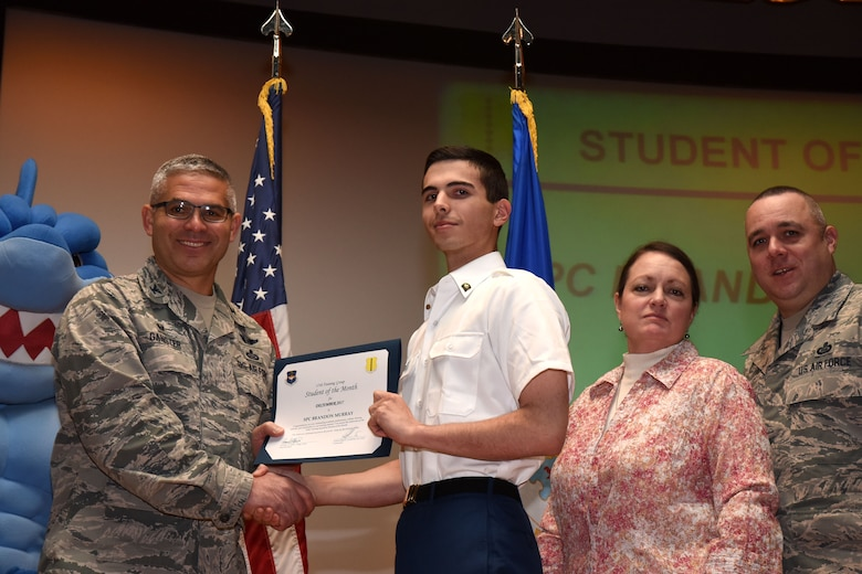 U.S. Air Force Col. Alex Ganster, 17th Training Group commander, presents the 316th Training Squadron Student of the Month award for Dec. 2017 to U.S. Army Spc. Brandon Murray, 316th TRS trainee, in the base theater on Goodfellow Air Force Base, Texas, Jan. 5, 2018. The 316th Training Squadron's mission is to conduct U.S. Air Force, U.S. Army, U.S. Marine Corps, U.S. Navy and U.S. Coast Guard cryptologic, human intelligence and military training. (U.S. Air Force photo by Airman 1st Class Seraiah Hines/Released)