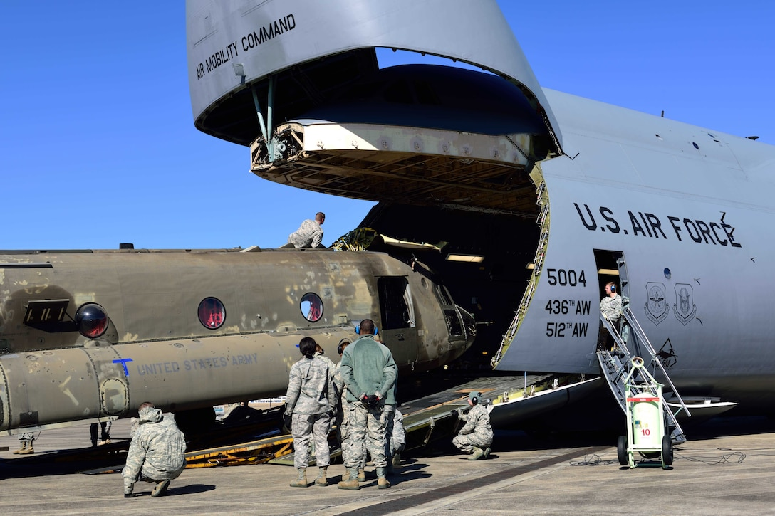 Reservists from the 41st Aerial Port Squadron and other service members from various units load a CH-47 Chinook helicopter onto a C-5M Super Galaxy from the 709th Airlift Squadron at the Gulfport Combat Readiness Training Center – Battlefield Airman Center, Miss., Jan. 6, 2018. Reservists, guardsmen, civilians and active-duty members from the Air Force, Army and Navy worked side by side during this training event called Breaking Barriers GRIP III Jan. 5-7, highlighting the joint effort of this training opportunity. (U.S. Air Force photo by Tech. Sgt. Ryan Labadens)