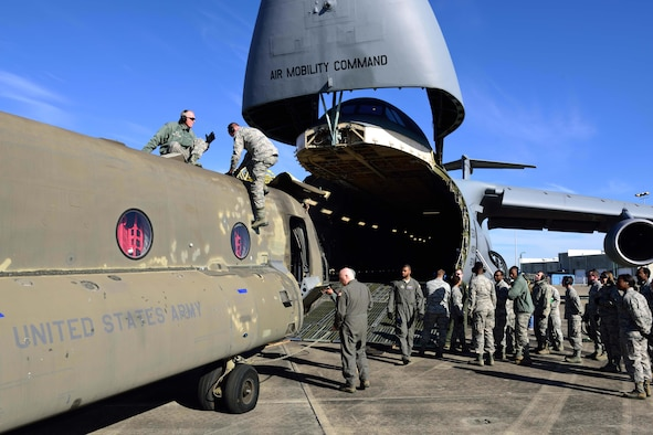 Reservists from the 41st Aerial Port Squadron and other service members from various units prepare to load a CH-47 Chinook helicopter onto a C-5M Super Galaxy from the 709th Airlift Squadron at the Gulfport Combat Readiness Training Center – Battlefield Airman Center, Miss., Jan. 6, 2018. Reservists, guardsmen, civilians and active-duty members from the Air Force, Army and Navy worked side by side during this training event called Breaking Barriers GRIP III Jan. 5-7, highlighting the joint effort of this training opportunity. (U.S. Air Force photo by Tech. Sgt. Ryan Labadens)