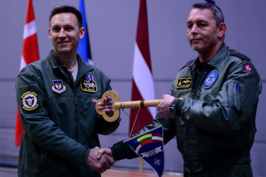 U.S. Air Force Lt. Col. Clint Guenther, 493rd Expeditionary Fighter Squadron detachment commander, presents the key to the Baltic Air Policing mission to Royal Dannish air force commander Col. Uffe Holstener during the official Baltic Air Policing hand-over, take-over ceremony at Šiauliai Air Base, Lithuania, Jan. 8, 2018. This is Denmark's sixth Baltic Air Policing rotation since operations began in 2004. (U.S. Air Force photo/ Tech. Sgt. Matthew Plew)