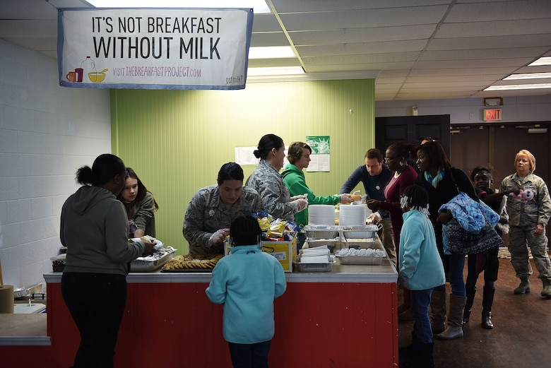 Members of the North Carolina Air National Guard (NCANG) serve food and drinks to families during Operation Santa at the Aristotle Preparatory Academy, Dec. 16, 2017. Operation Santa is a local and annual event run by the Chapter 7 organization of the North Carolina Air National Guard. This year, the NCANG provided presents, lunch, music, face-painting, blankets, stuffed animals. They partnered with the local Target for food donations and a craft table, and inflatable castles through Garris and Wilson Entertainment. (U.S. Air National Guard photo by Staff. Sgt. Laura J. Montgomery)