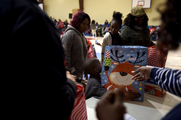 A young boy reaches for a present during Operation Santa held at the Aristotle Preparatory Academy, Dec. 16, 2017. Operation Santa is a local and annual event run by the Chapter 7 organization of the North Carolina Air National Guard. This year, the NCANG provided presents, lunch, music, face-painting, blankets, stuffed animals. They partnered with the local Target for food donations and a craft table, and inflatable castles through Garris and Wilson Entertainment. (U.S. Air National Guard photo by Staff. Sgt. Laura J. Montgomery)