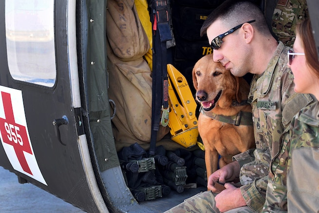 Army National Guardsmen and a military working dog sit inside a UH-60 Black Hawk medevac helicopter.