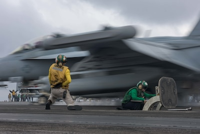 U.S. Navy Aviation Boatswain's Mate (Equipment) Airman Hailey Barela, right, and Lt. Cmdr. Robert Maul, from Springfield, New Jersey, signal the launch of an F/A-18E Super Hornet, assigned to Strike Fighter Squadron (VFA) 195, on the flight deck aboard the Navy's forward-deployed aircraft carrier, USS Ronald Reagan (CVN 76) during the Carrier Air Wing Five fly-off in the Pacific Ocean in waters south of Japan Nov. 28, 2017. The Ronald Reagan, the flagship of Carrier Strike Group 5, provides a combat-ready force that protects and defends the collective maritime interests of allies and partners in the Indo-Asia-Pacific region. (U.S. Navy photo by Mass Communication Specialist 2nd Class Kenneth Abbate)