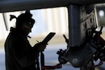 Aircraft maintenance airman reviews instructions on the flight line.