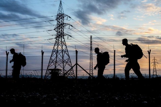 Three soldiers, shown in silhouette against a blue and pink sky, walk past an electrical tower.
