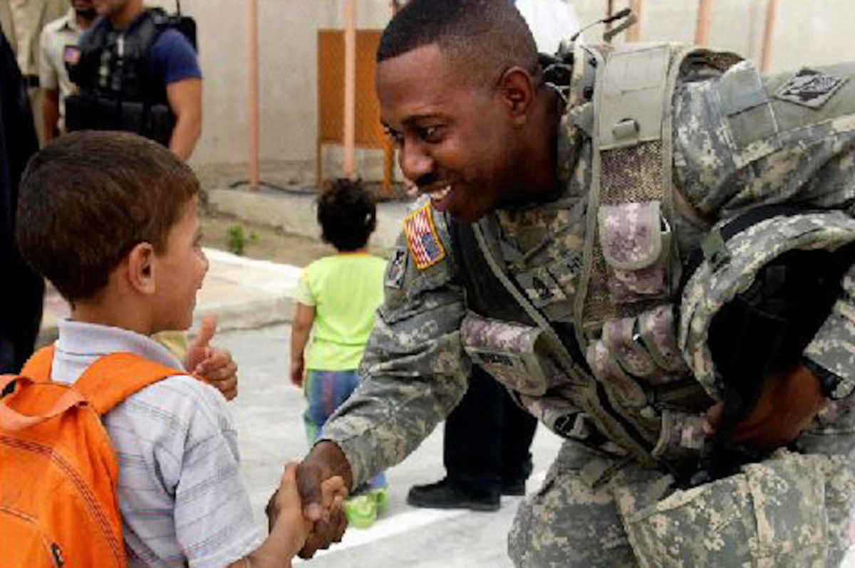 Army Sgt. Maj. Benny Hubbard shakes hands with an Iraqi child