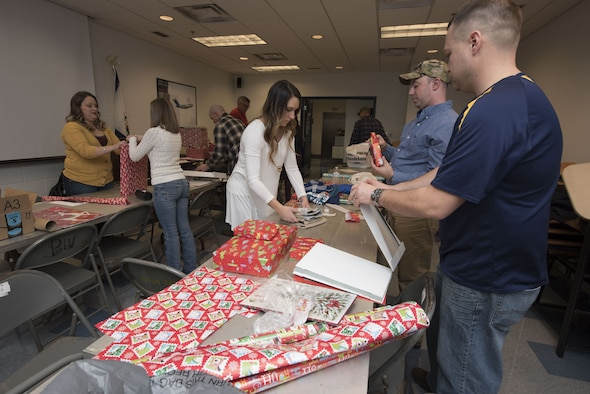 Members of the 167th Operations Group wrap and organize gifts for children in the tri-county area as part of the Ops Adopts program headed up by First Lt. Ryan Day, a pilot for the 167th Airlift Wing, at far right in photo, in the Operations building at the 167th Airlift Wing, Martinsburg, W.Va., Dec. 15. (U.S. Air National Guard photo by Senior Master Sgt. Emily Beightol-Deyerle)