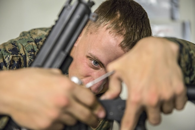 A Marine uses both hands to remove a rifle hammer while staring intently at it.