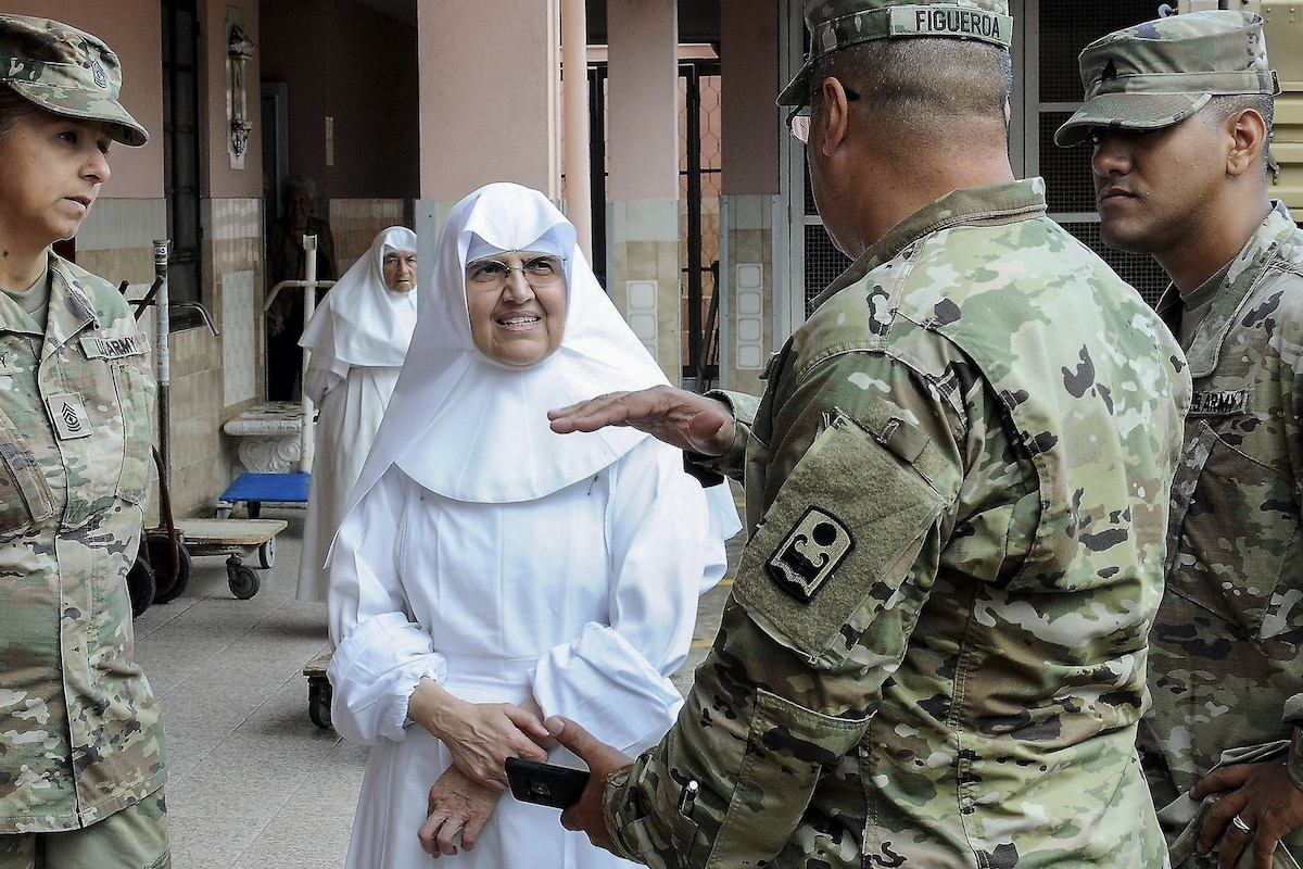 A soldier gesticulates while speaking to a nun and fellow soldiers outside a building.